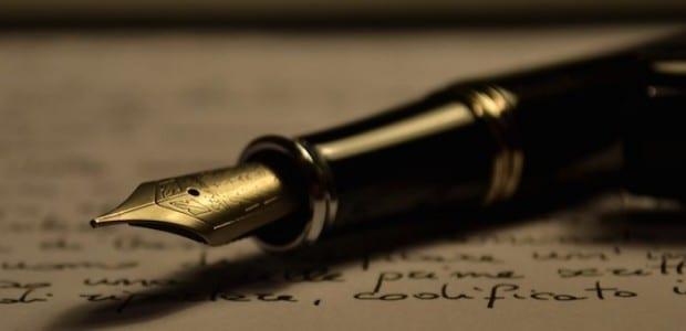 Bilden visar en gammaldags penna mot ett papper