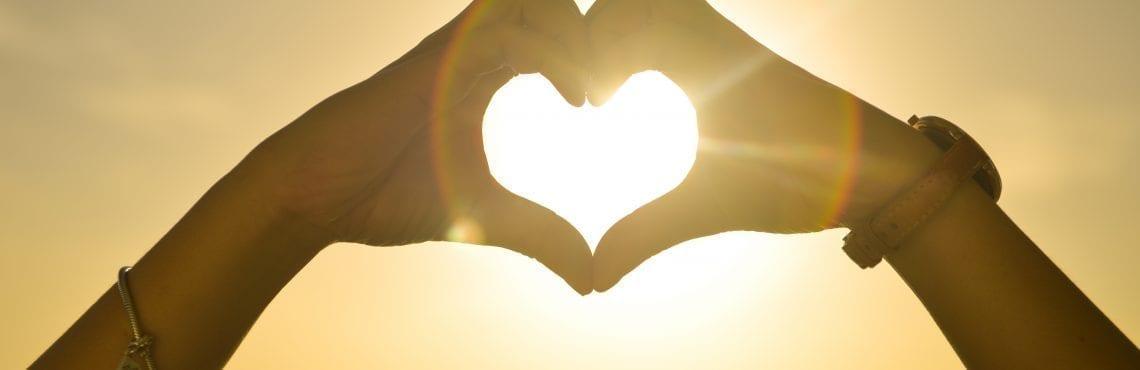 Bilden visar två händer som formar ett hjärta mot solen.