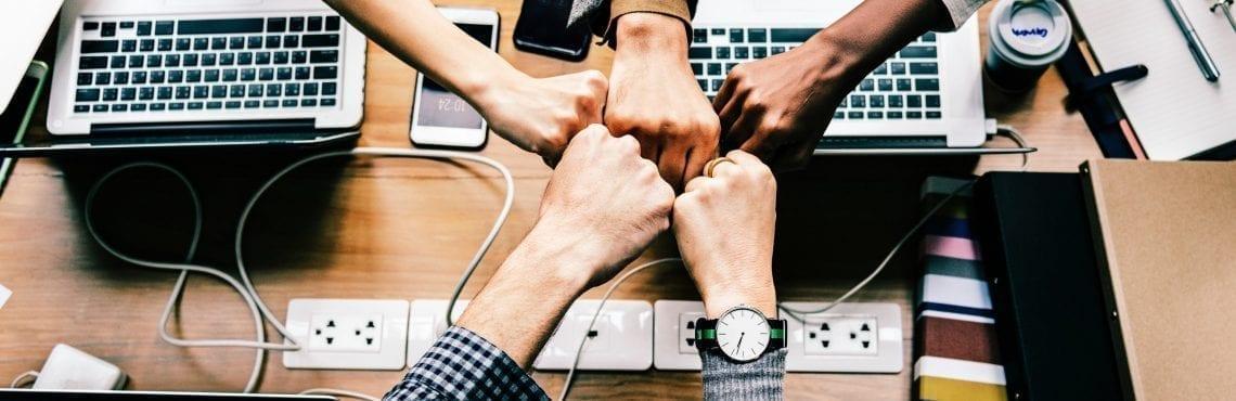 Bilden visar fem händer som gör en fist bump.