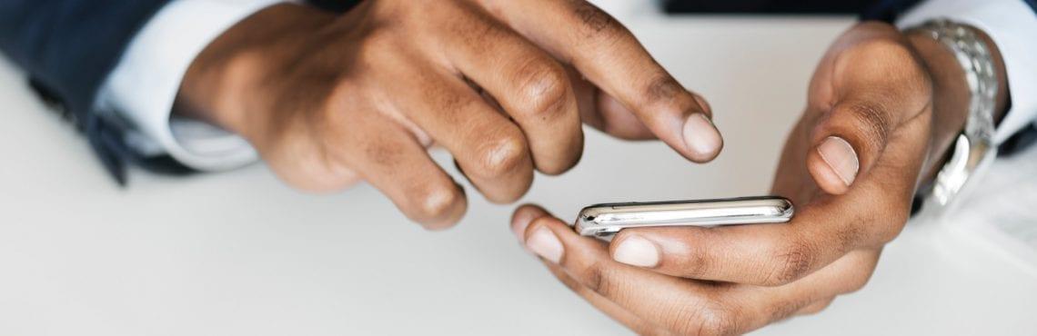 Bilden visar en persons händer som arbetar på en mobiltelefon.