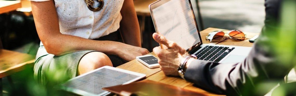 Två personer sitter och pratar om konvertering. På bordet ligger en dator, en padda och en telefon också.