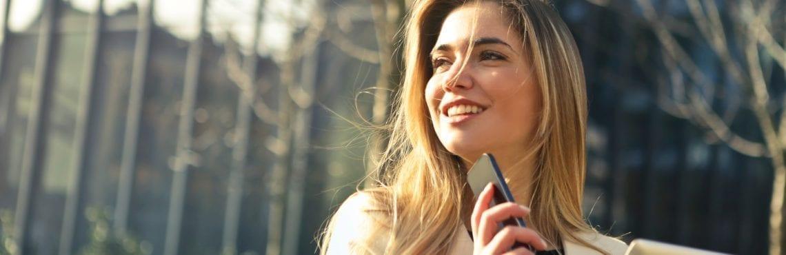 Bilden visar en leende kvinna som håller i en telefon och en padda.