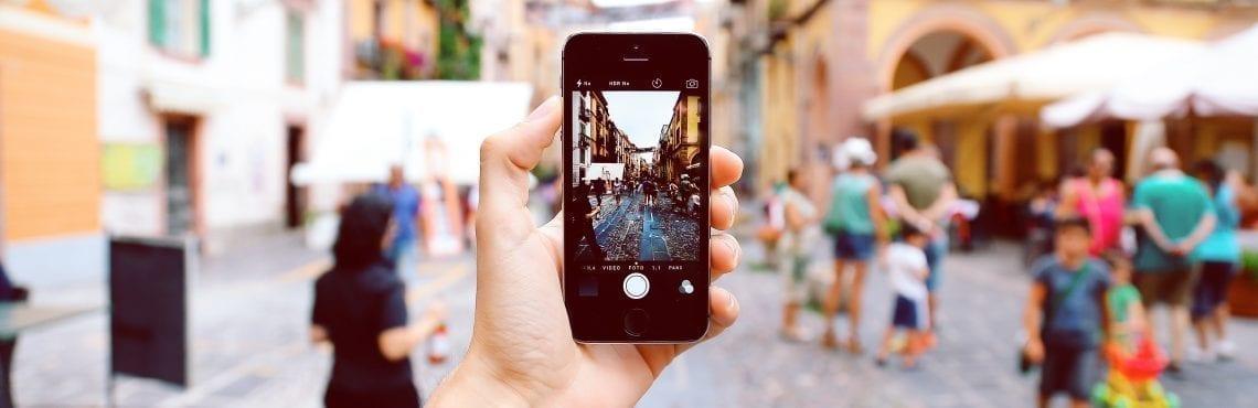 Bilden visar en hand som håller i en mobiltelefon och är på väg att ta ett kort.