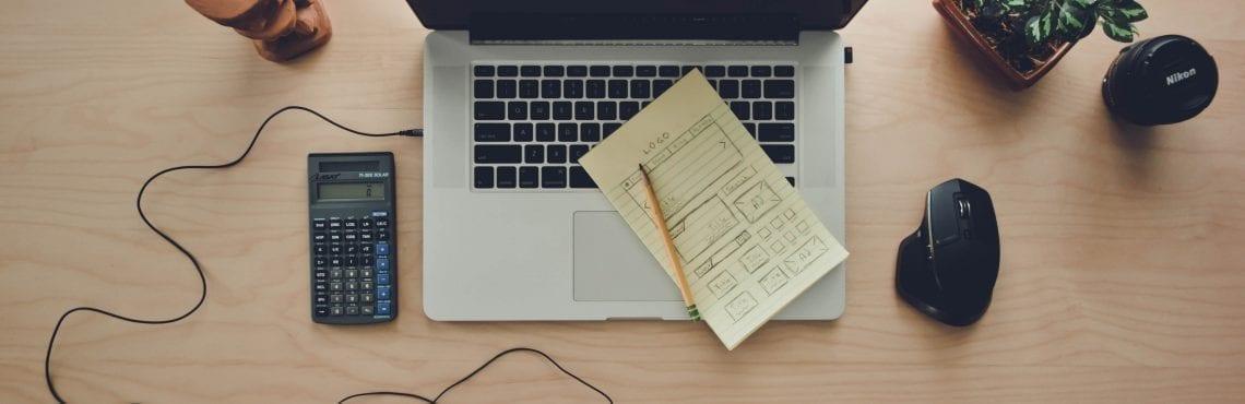 Bilden visar en laptop på en skrivbord. Runt om ser vi en mus, miniräknare, hörlurar och en ritad sitemap.