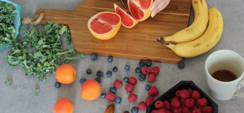 A cutting board with oranges, mandarins, berries, bananas and a coffee cup