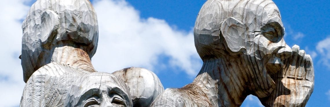 The heads of three wooden statues in front of the sky